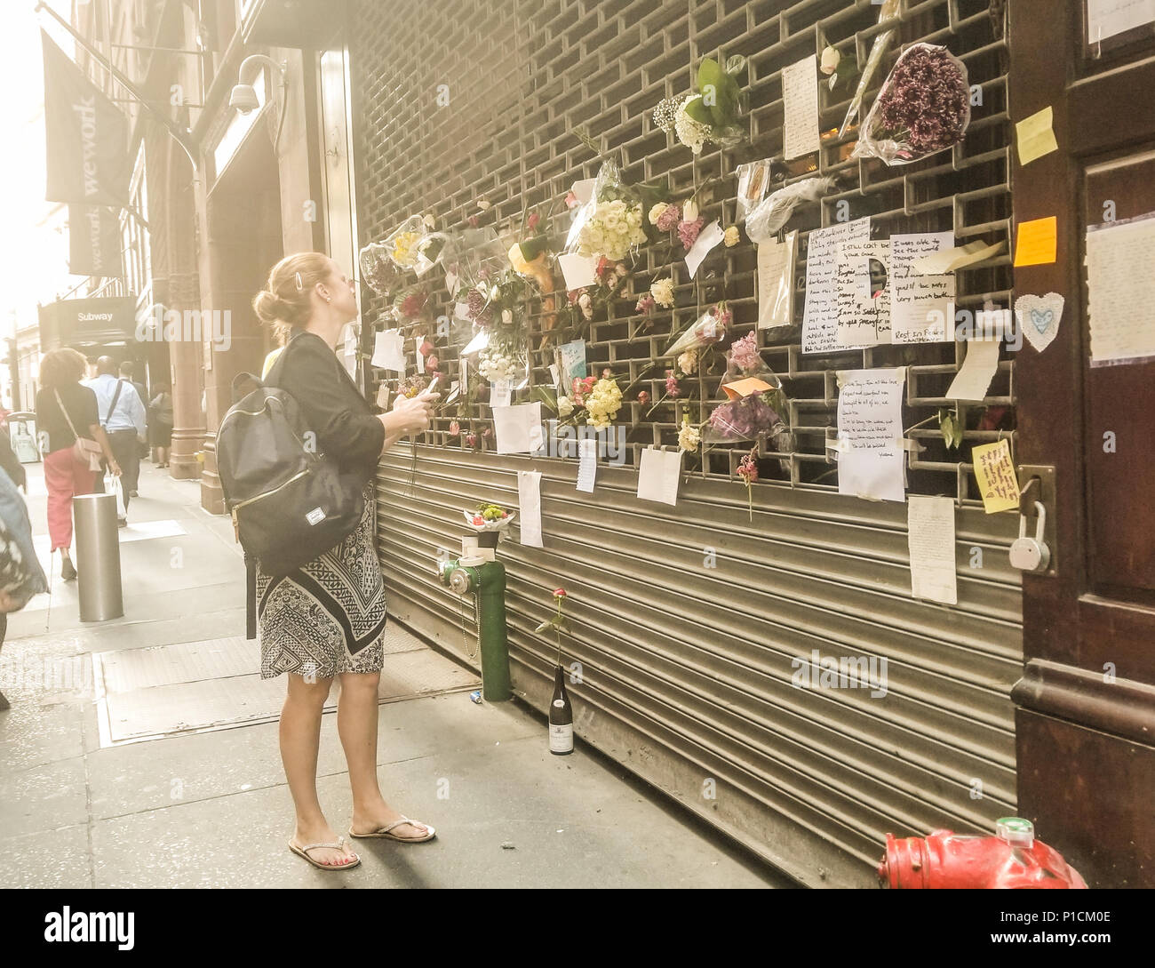 New York, USA, 11th June 2018. A woman observes handwritten notes and flowers left, memorializing Anthony Bourdain after his shocking suicide on June 8, 2018. Passersby and fans left items at the downtown location of the Les Halles restaurant, most well-known for being one of the first restaurants to give celebrity chef, author, and television host a start to his cooking career (he worked at the midtown location). Credit: Brigette Supernova/Alamy Live News - Stock Image