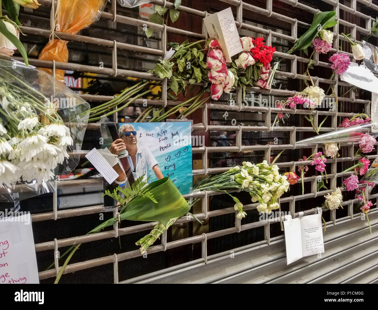 New York, USA, 11th June 2018. Handwritten notes and flowers left, memorializing Anthony Bourdain after his shocking suicide on June 8, 2018. Passersby and fans left items at the downtown location of the Les Halles restaurant, most well-known for being one of the first restaurants to give celebrity chef, author, and television host a start to his cooking career (he worked at the midtown location). Credit: Brigette Supernova/Alamy Live News - Stock Image