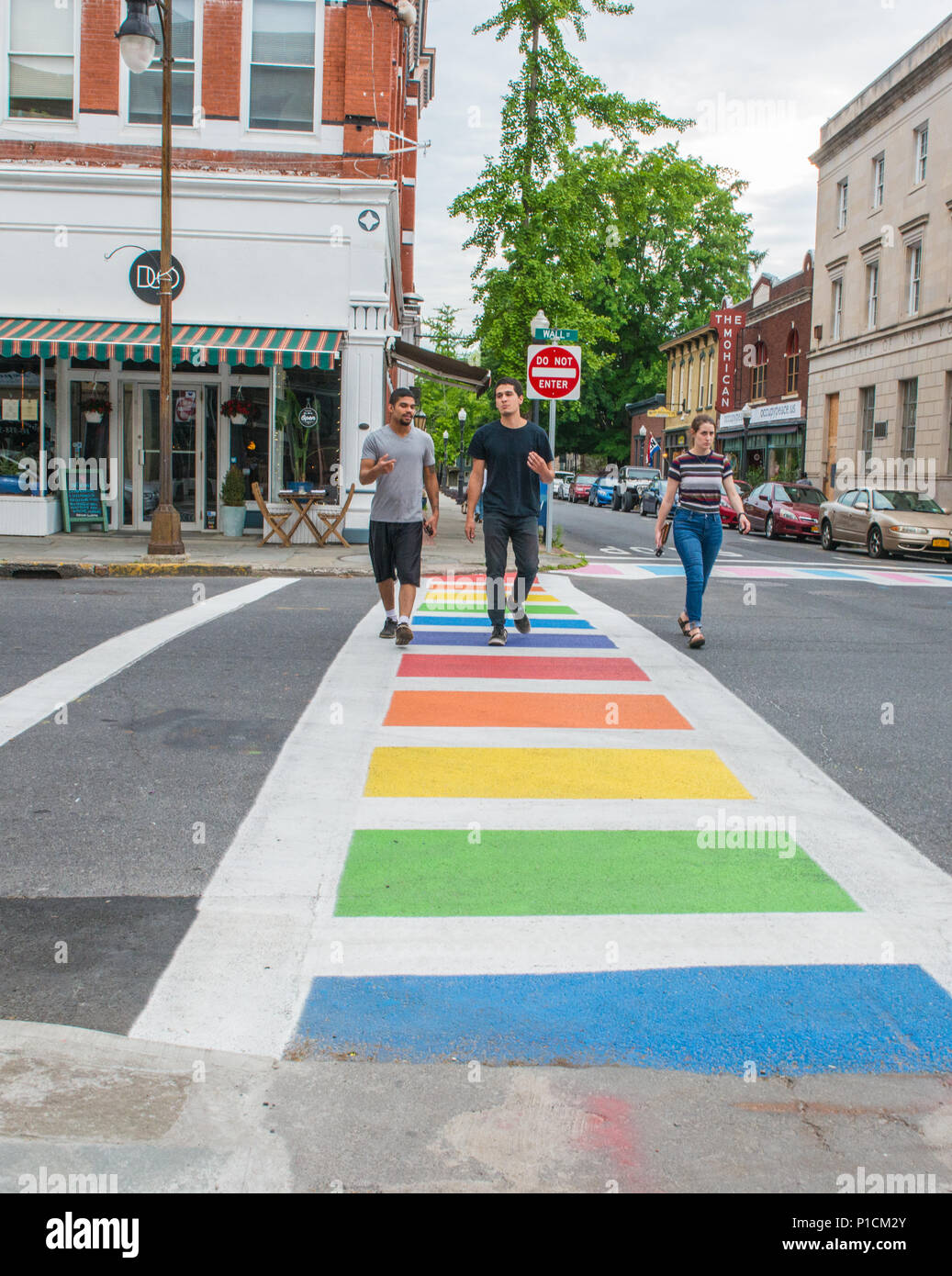 Three people cross the street, outside the Hudson Valley LGBTQ Community Center in Kingston, New York, the crosswalks are painted with the colors of the gay pride and transgender flag, and the original gay pride flag sporting eight colors flies outside the headquarters - Stock Image