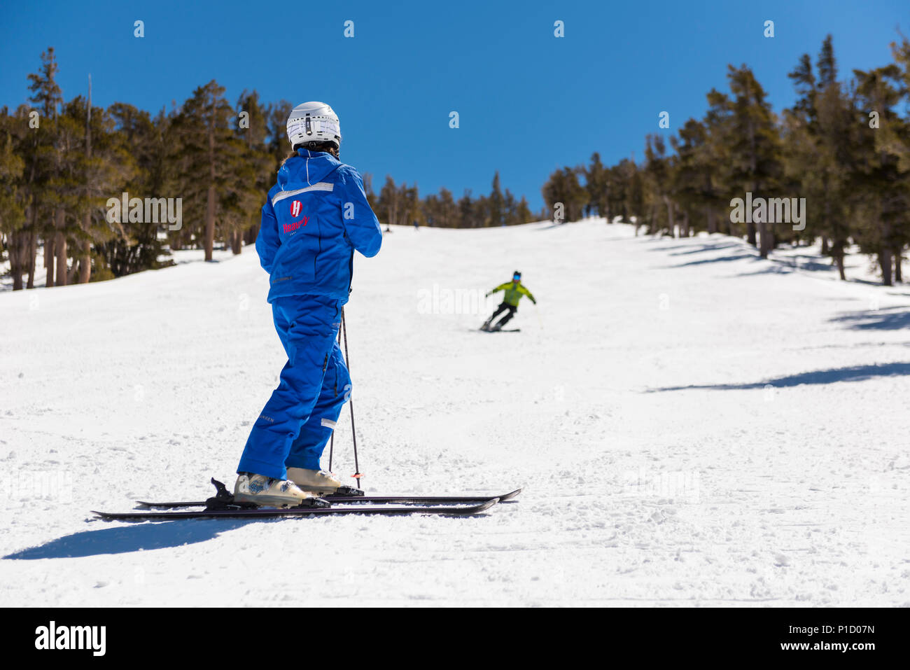 Heavenly ski instructor watches a student doing a short radius turn drills at the Heavenly Valley Ski Resort ski school in South Lake Tahoe, USA. - Stock Image