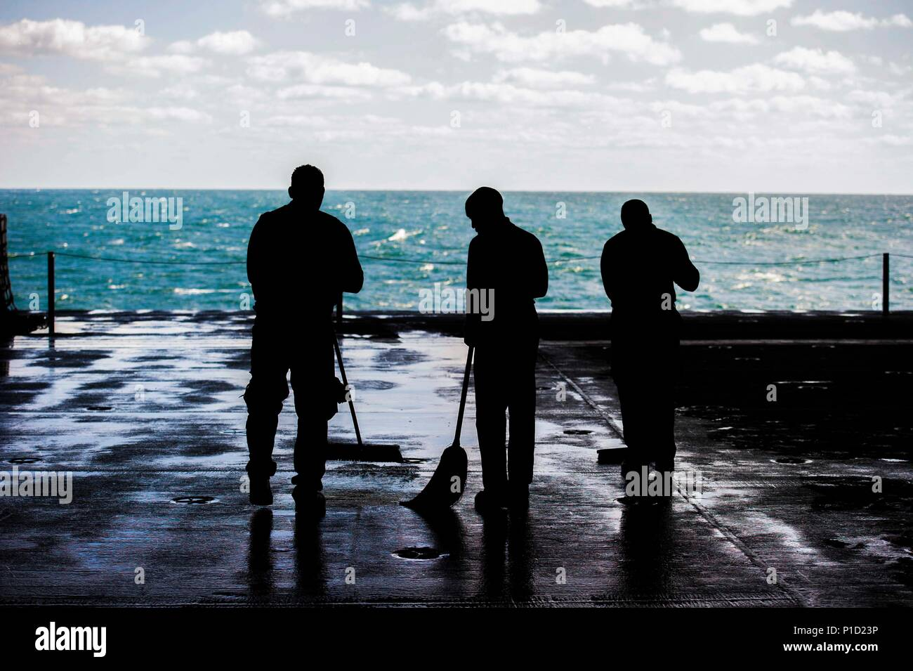 161014-N-RG522-016 ATLANTIC OCEAN (Oct. 14, 2016) Sailors sweep the hangar bay after a countermeasure washdown drill aboard the aircraft carrier USS George Washington (CVN73). George Washington, homeported in Norfolk, is underway in the Atlantic Ocean. (U.S. Navy photo by Seaman Jonathan Price) - Stock Image