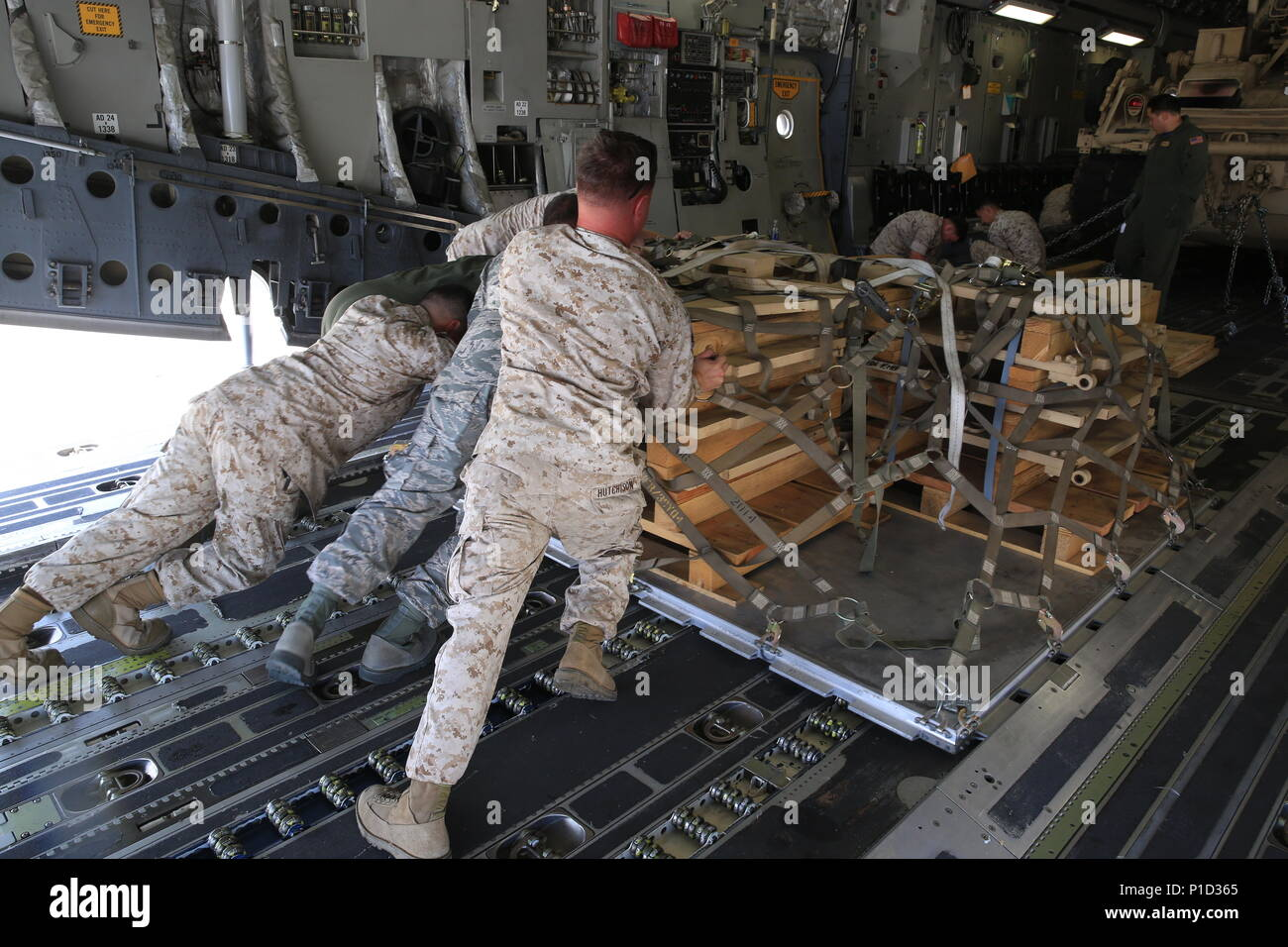 U.S. Marines and Airmen work hand-in-hand to load a pallet, filled with an M-88A2 HERCULES' armored side skirts and front winch aboard the C-17 Globemaster III at March Air Reserve Base, Calif., Oct. 14, 2016. The C-17 flew to Marine Corps Air Ground Combat Center Twentynine Palms, Calif., to deliver the M-88A2 recovery vehicle for use by Combat Logistics Company 13. - Stock Image