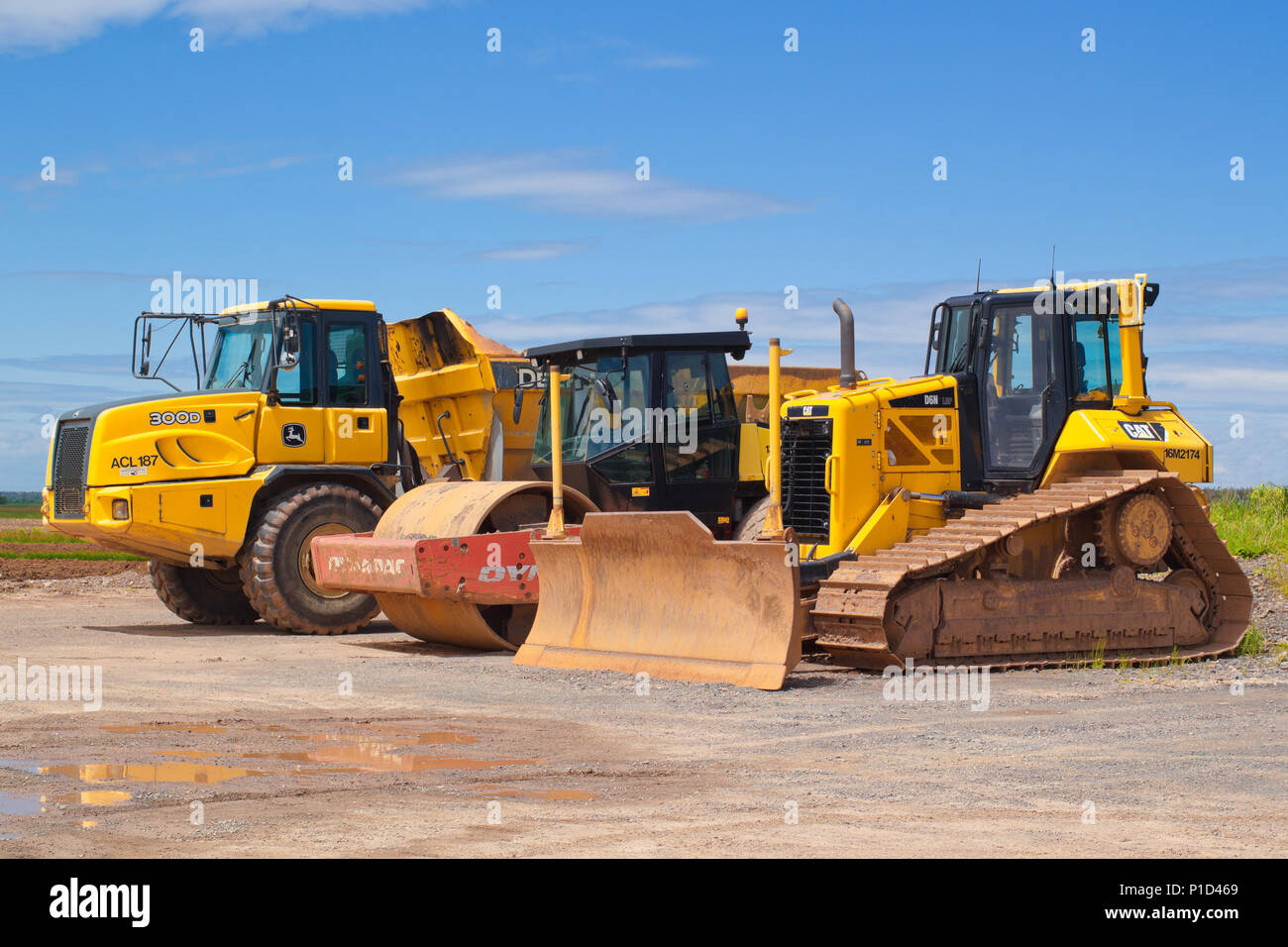 TRURO, CANADA - JUNE 10, 2018: Caterpillar bulldozer, Dynapac roller and John Deere dump truck parked outside on a sunny day. - Stock Image