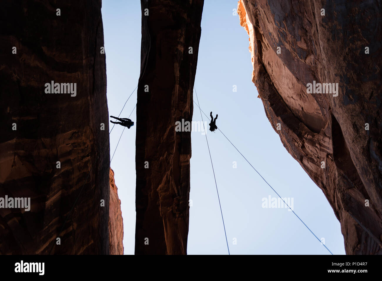 People rappelling from an arch in Moab, Utah. - Stock Image