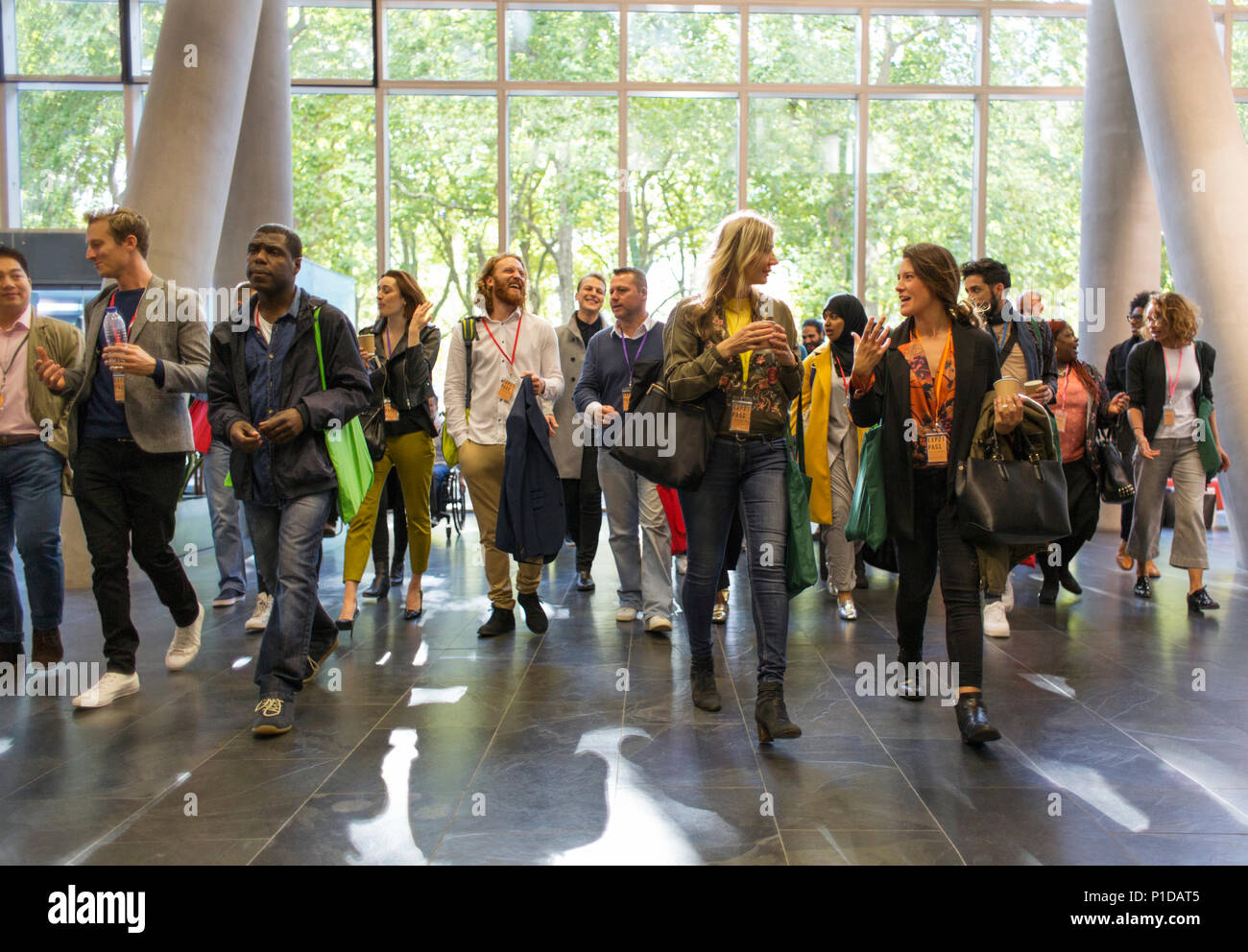 Business people arriving at conference, walking in lobby - Stock Image