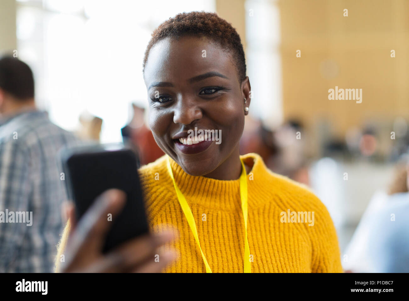 Smiling businesswoman using smart phone - Stock Image