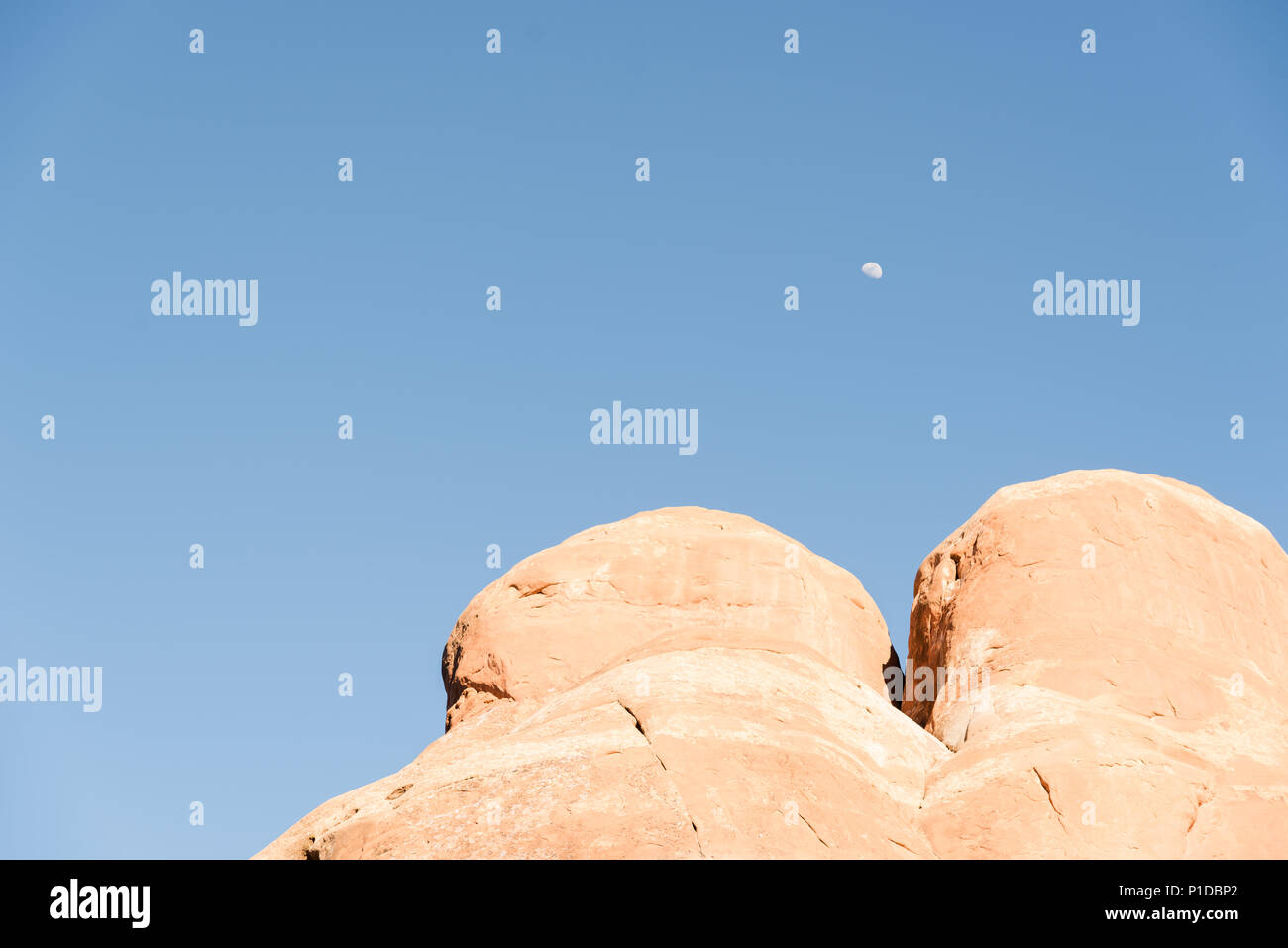 The moon between tow boulders in Arches National Park, Utah. - Stock Image