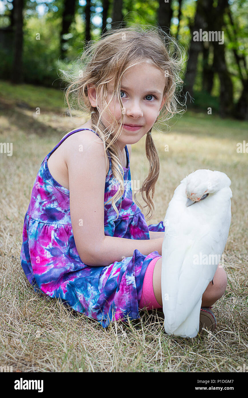 A young girl and a bare eyed cockatoo. - Stock Image