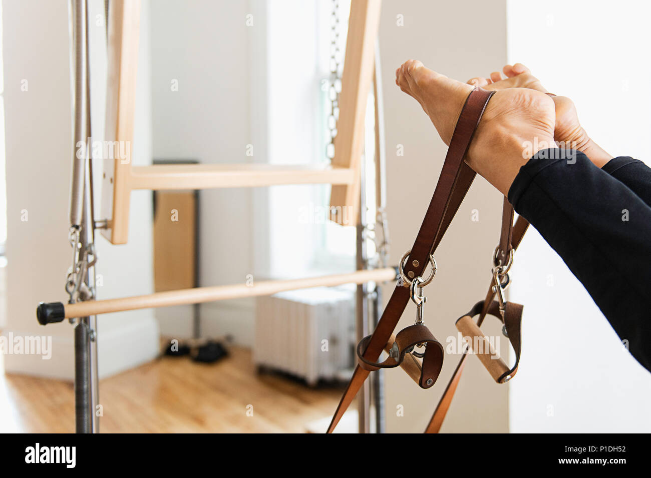 A woman working out on a reformer. - Stock Image