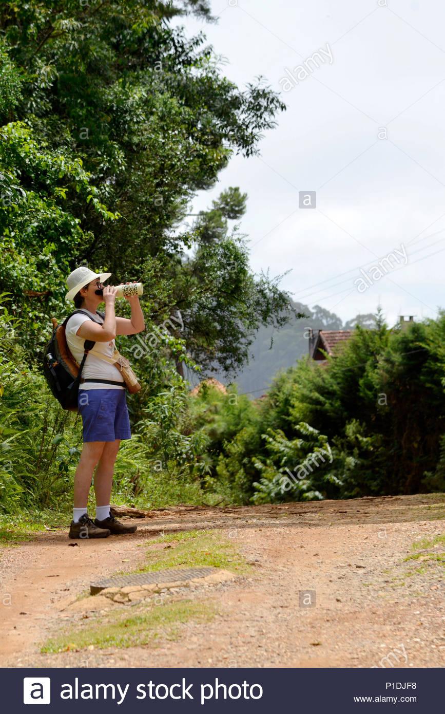 Person, Ecotourist, Drinking Water, Hiking, district of Monte Verde, Serra da Mantiqueira, 2018, Camanducaia, Minas Gerais, Brazil. Authorized Image U - Stock Image