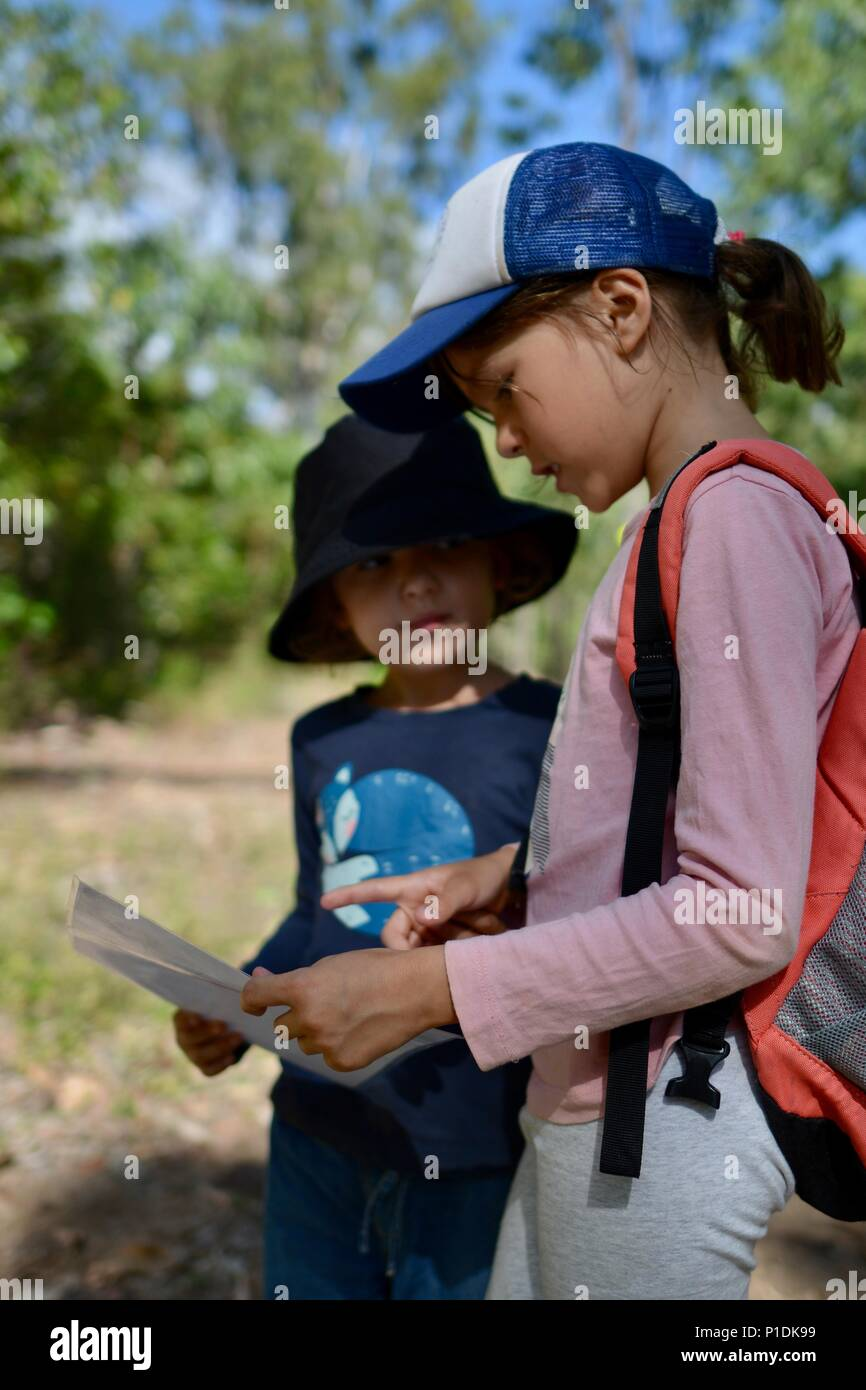Two children look at a map to decide where they have to go on a track, Paluma Range National Park, Rollingstone QLD, Australia - Stock Image