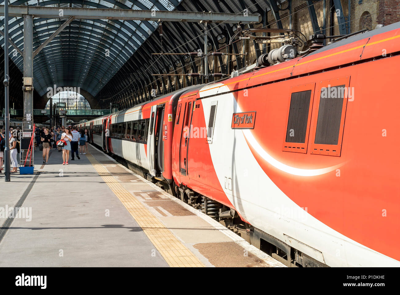 Passengers boarding a Virgin East Coast service at London Kings Cross. The UK Government has now taken control of this privatized route. - Stock Image