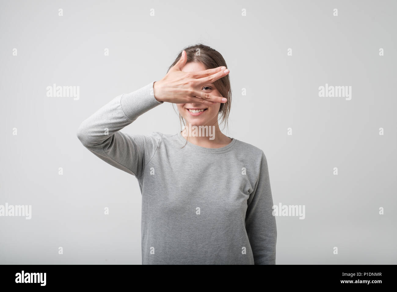 Young happy european female covering her face using hands. - Stock Image