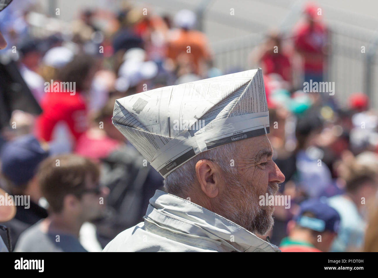Old man in a crowd with a newspaper sailor hat Stock Photo