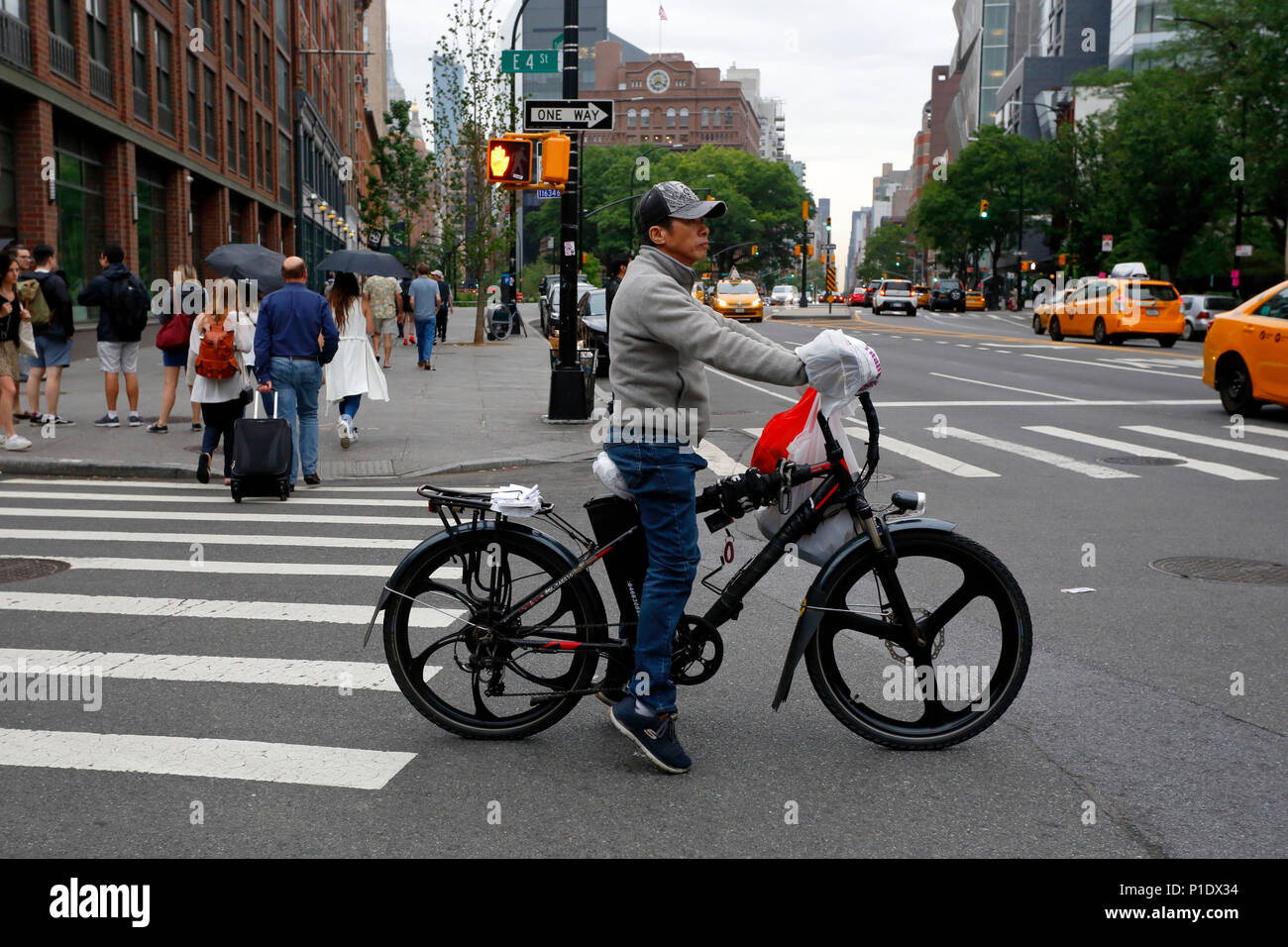 A Nyc Food Delivery Person On An Electric Bicycle Stock Photo
