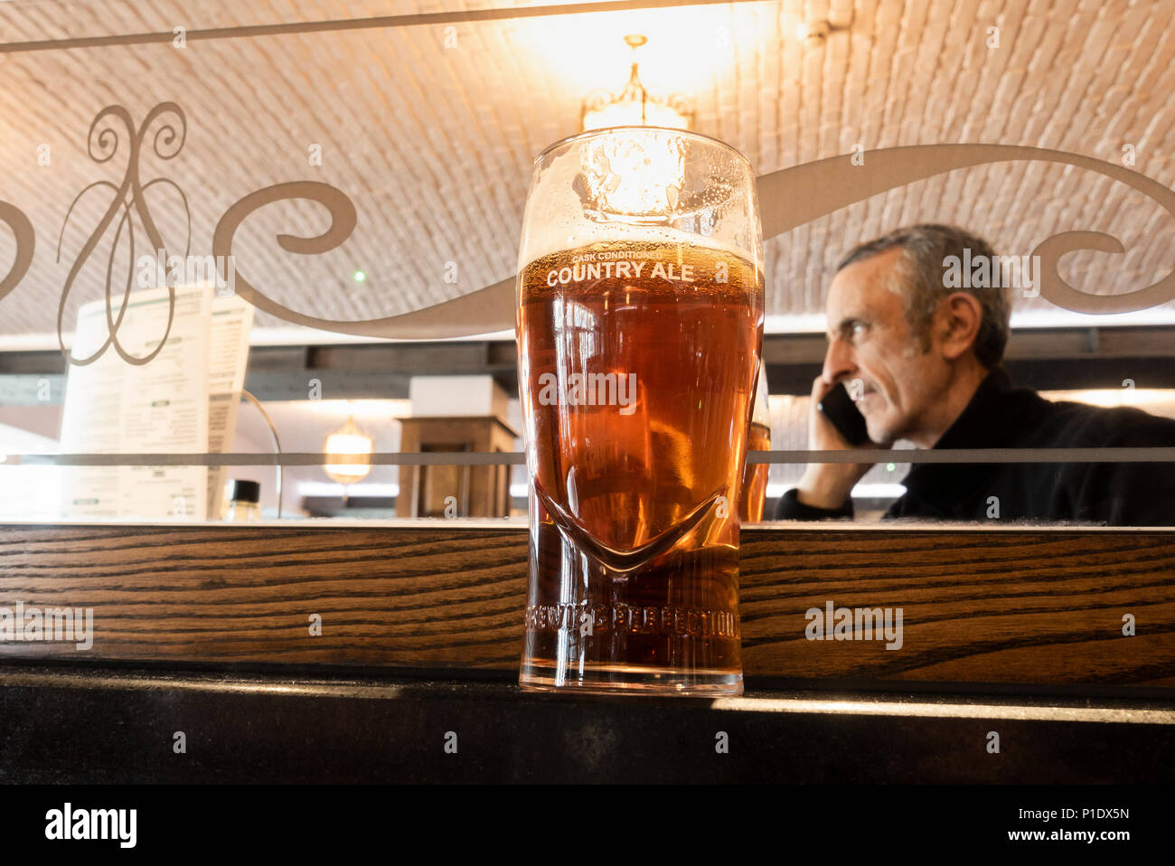 Mature man with pint of craft beer talking on mobile phone in JD Wetherspoon pub in England. UK - Stock Image