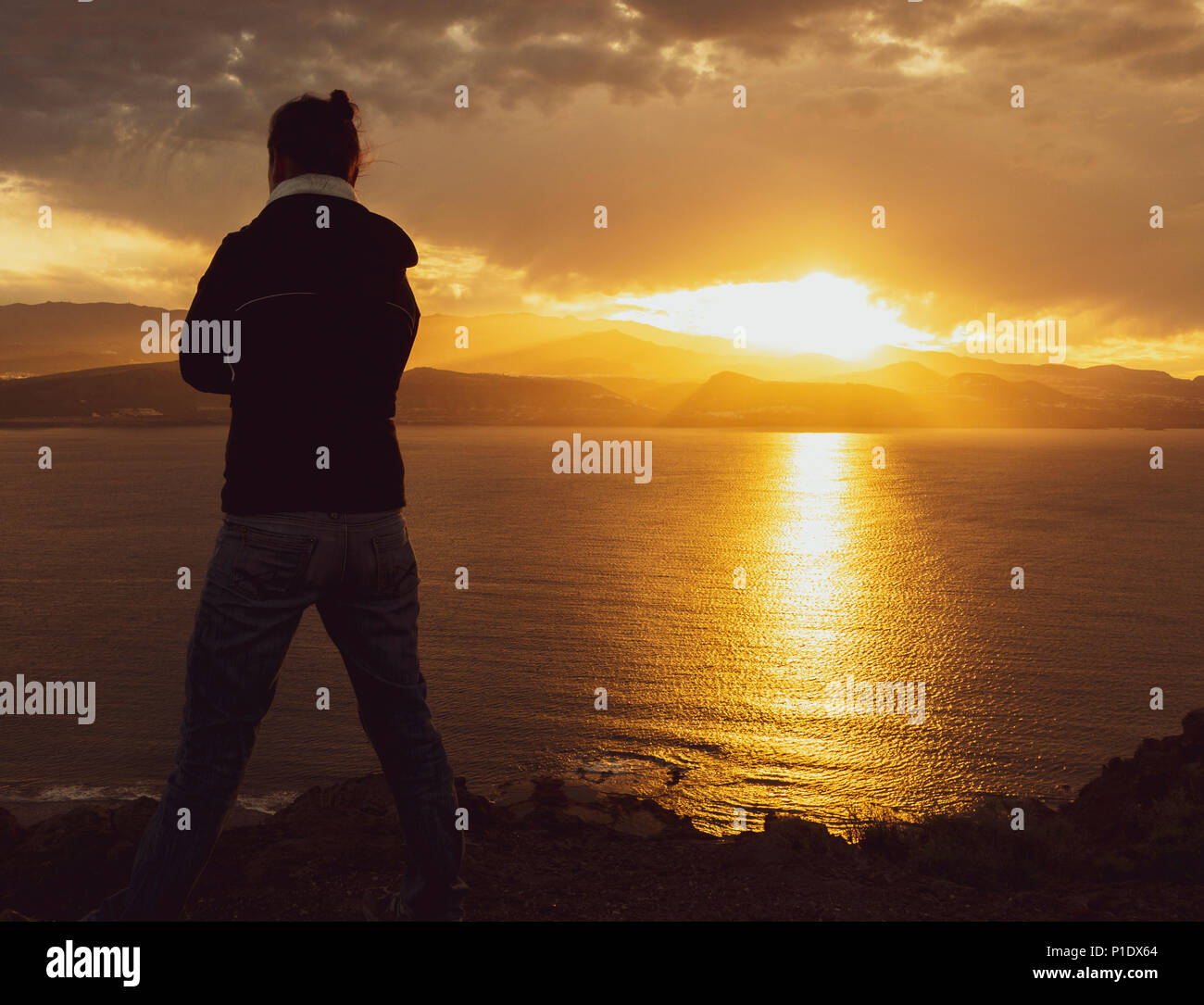 Rear view of woman looking out over the sea from high cliffs at sunset. Female mental health/depression, mental illness,loneliness...,concept image - Stock Image