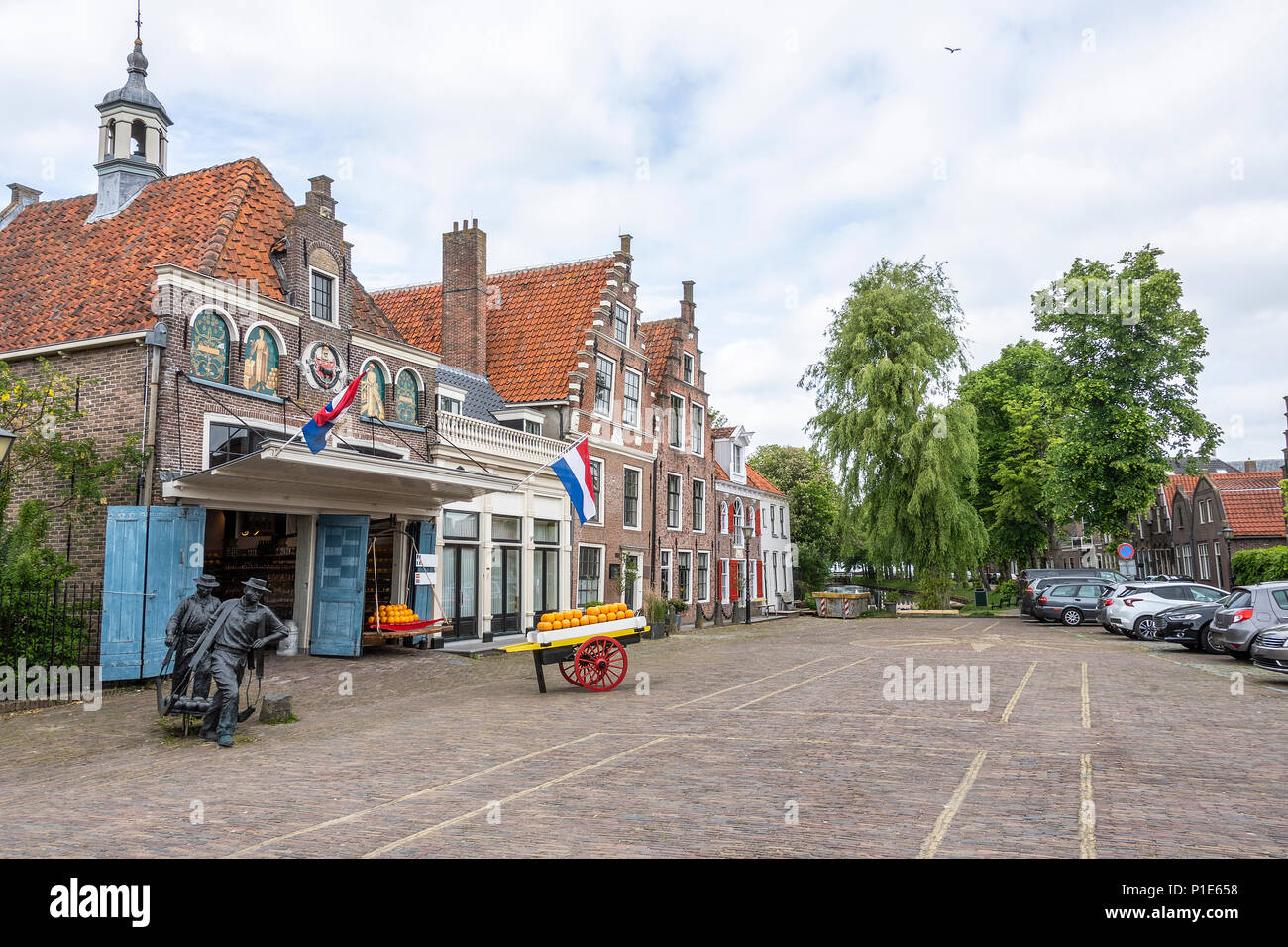 square with its traditional cheeses and houses and in the background a canal in the village of edam. netherlands - Stock Image
