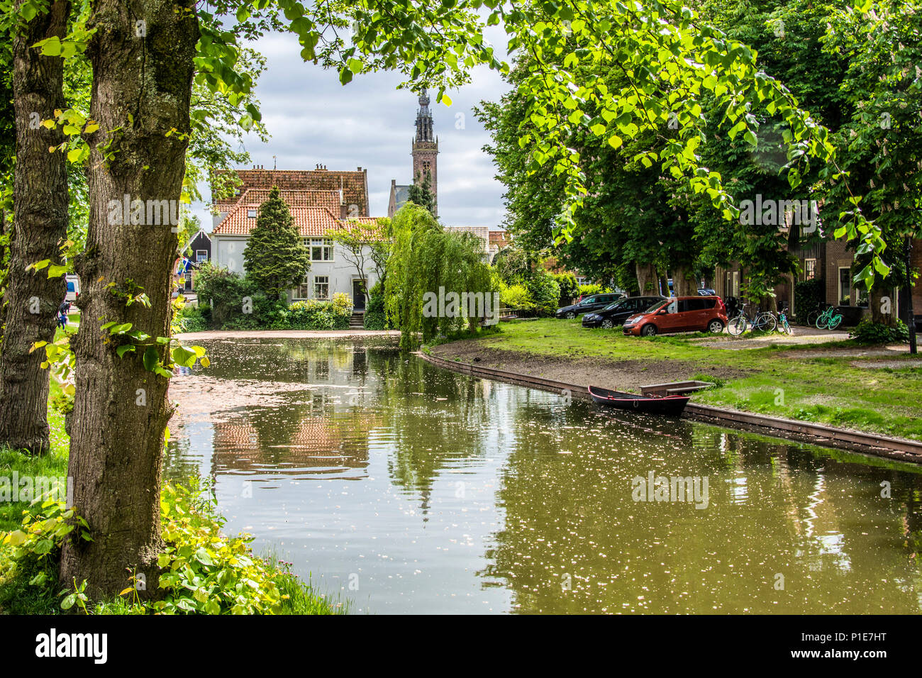 Classic Dutch landscape with calm water canal boat and in the background the dome of the church of the village of Edam Netherlands - Stock Image
