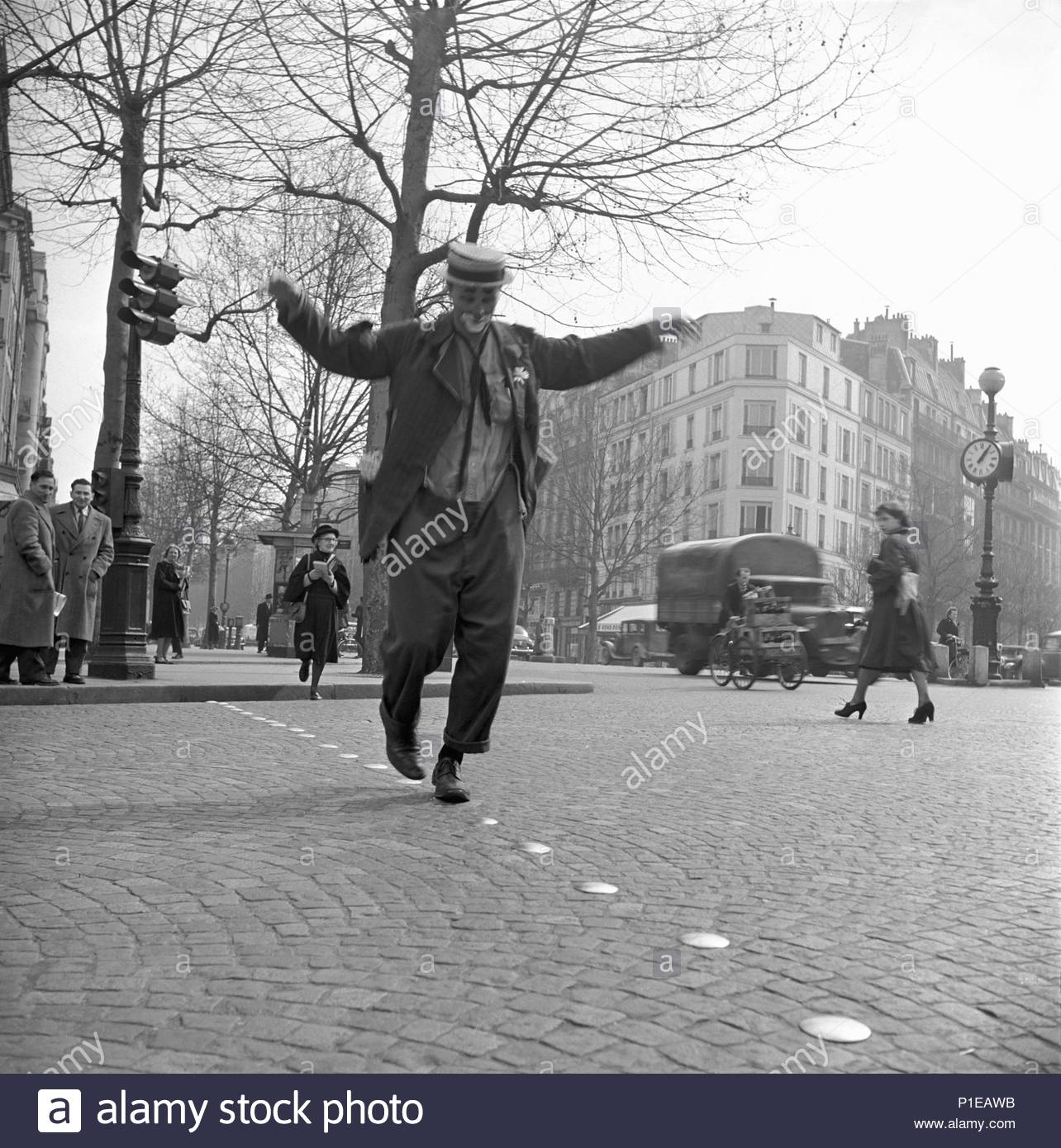 An American in Paris: Frank Billerbeck tries out his new clown routine in the streets of Paris, 1952. Location: Townscape, Paris, France. - Stock Image