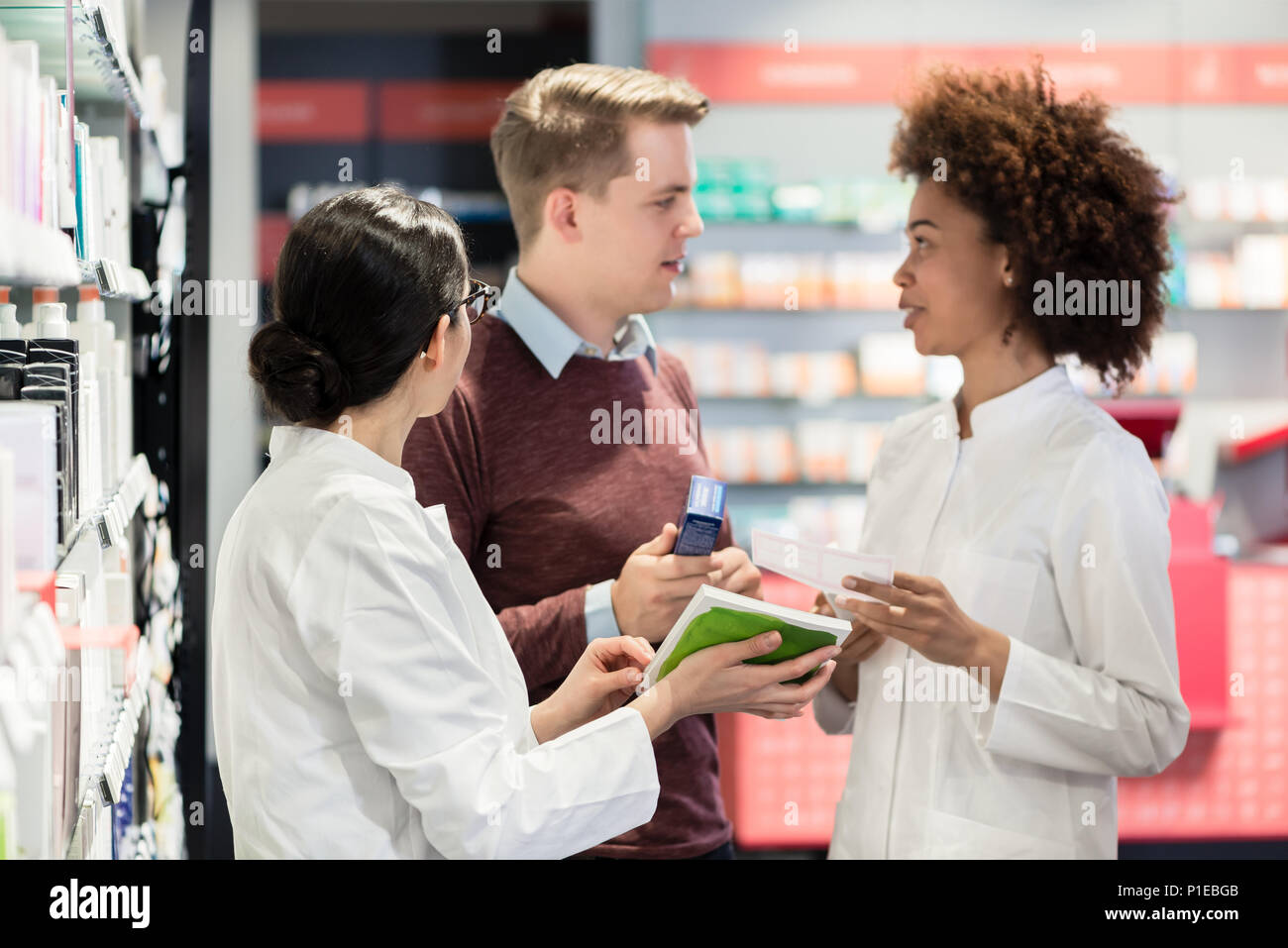 Portrait of a female experienced pharmacist reading the indications - Stock Image