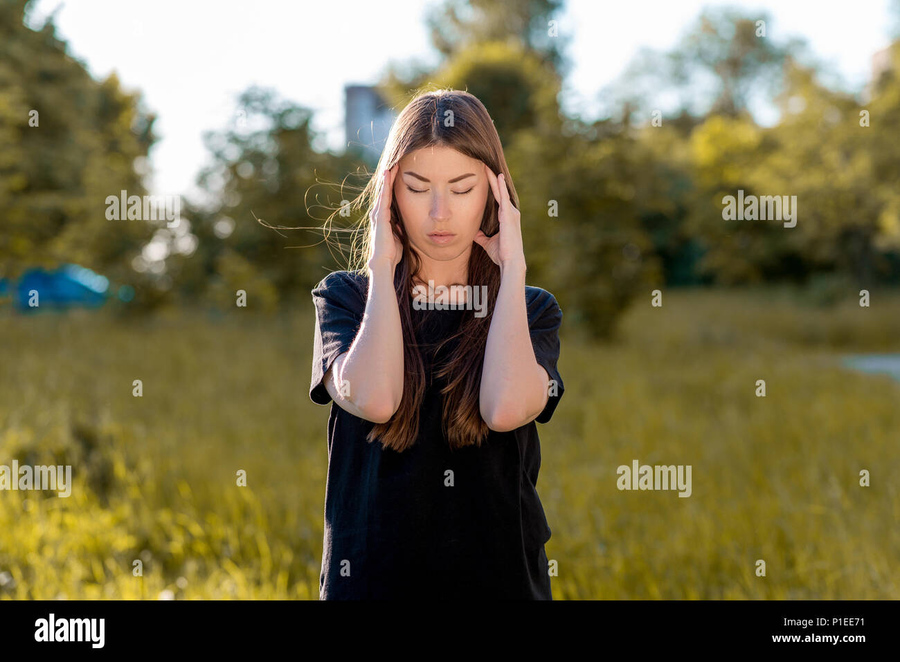 Girl brunette in the fresh air. Holds his hands around his head. Headache. Tries to concentrate. Migraine and severe pain. In the summer in the park dressed in casual clotting. - Stock Image