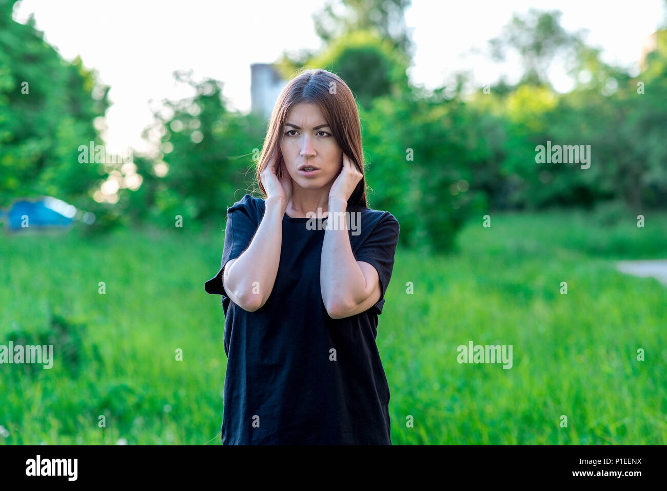Girl summer in the park in fresh air. Hands showing a gesture closing his ears. Loud noise of discontent. Unwillingness to listen to the interlocutor. - Stock Image