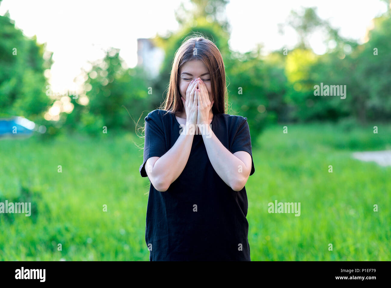 The brunette girl in summer outdoors. In a black T-shirt everyday wear. He covers his mouth with his hands. Happy laughing laughs with her hands over her mouth. Emotions of happiness and pleasure. - Stock Image
