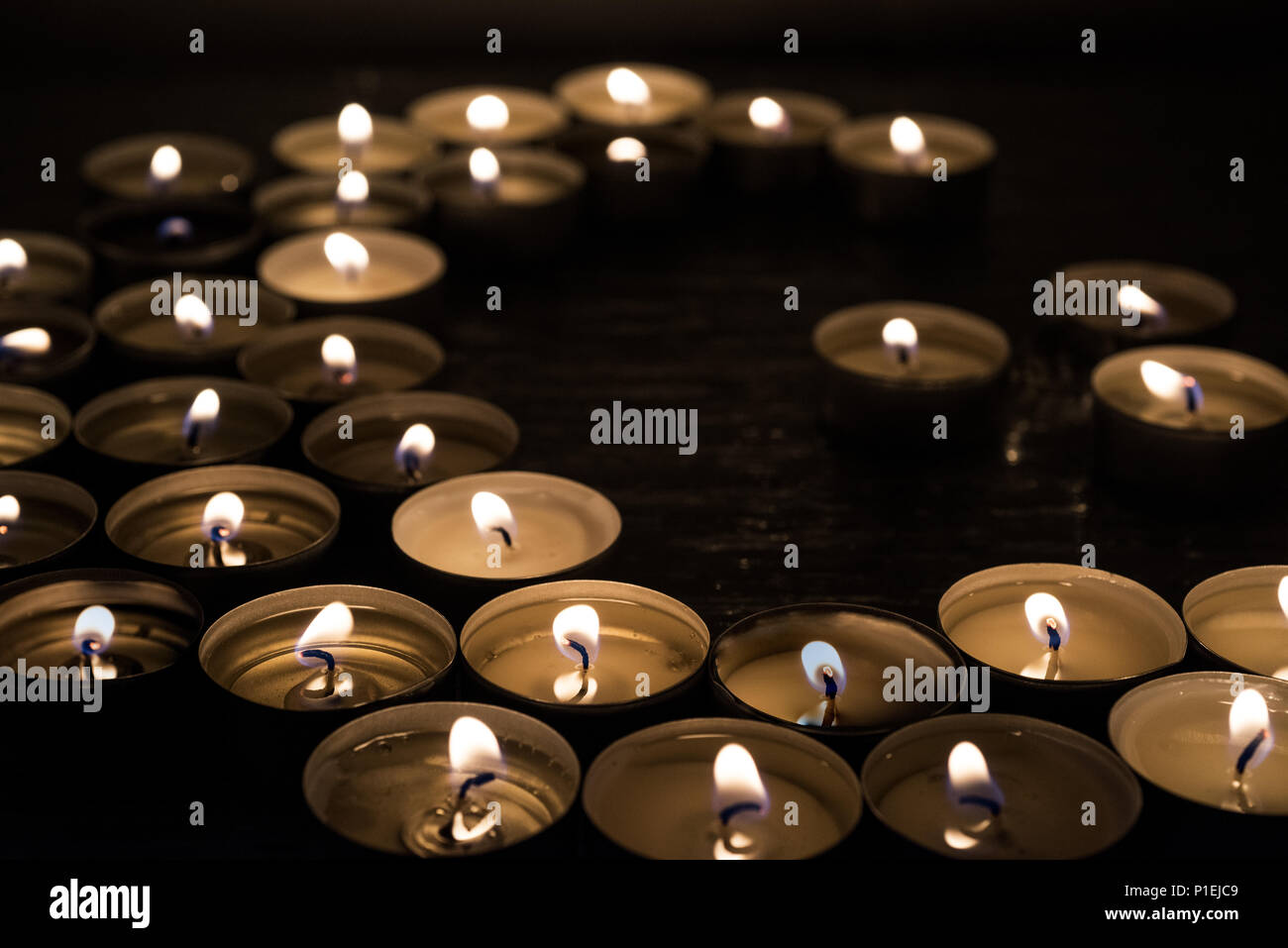 Symbols of Islam. Candle lights on black background. Abstract isolated photo. - Stock Image