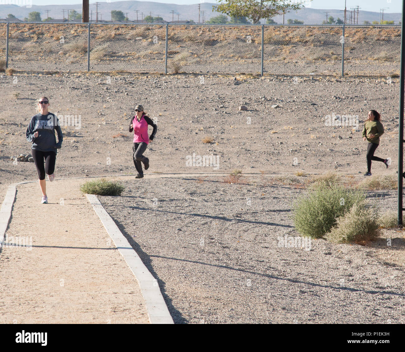 Ashley Ignatz takes the lead, with Jamie Teale and Jennifer Wolef close behind, during the running portion of the modified Combat Fitness Test the wives participated in during Jane Wayne Day aboard Marine Corps Logistics Base Barstow, Calif., Oct. 14. The event gives military spouses the opportunity to experience life as a Marine for a day. - Stock Image