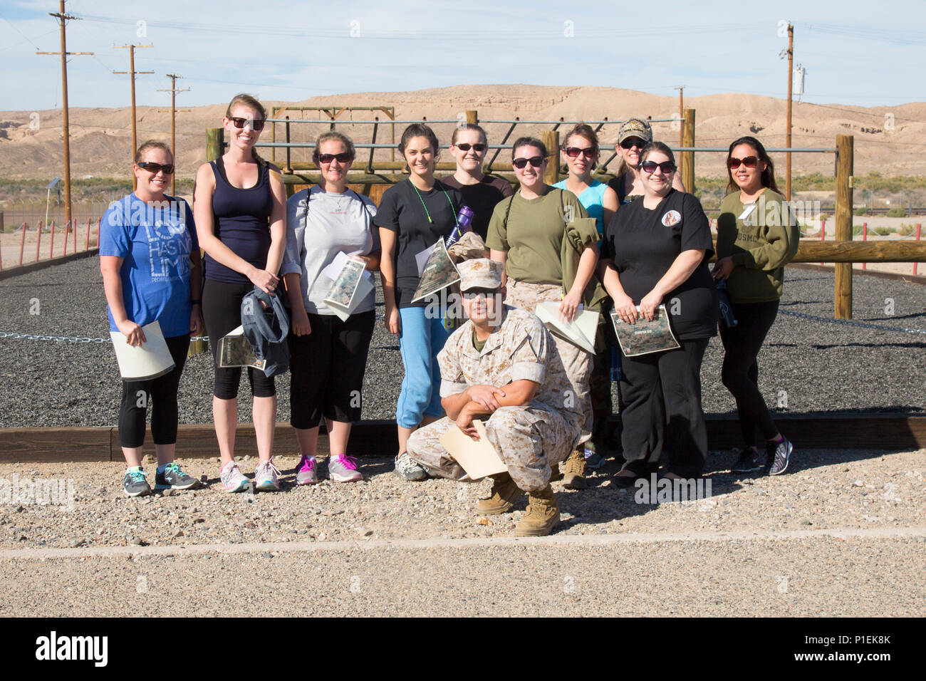 Chief Warrant Officer Jose Maynes poses for a group shot with the military spouses who participated in Jane Wayne Day aboard Marine Corps Logistics Base Barstow, Calif., Oct. 14. Military spouses left to right: Amanda Roselli, Ashley Ignatz, Jill Kovach, Miranda Williams, Casey Carlson, Erica King, Jessica Kenny, Jamie Teale, Jennifer Lee, Jennifer Wolef. - Stock Image