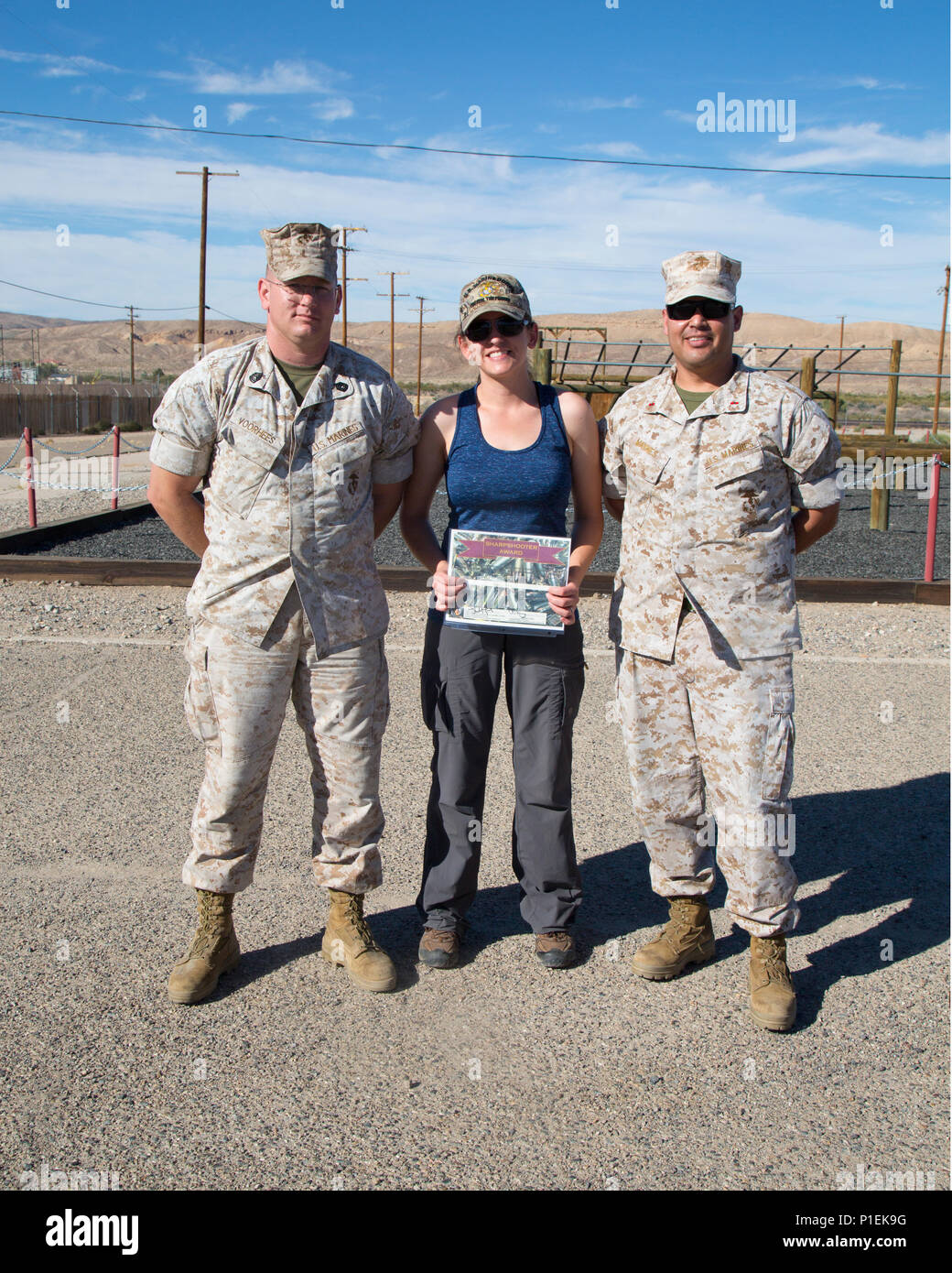 Jamie Teale poses with Gunnery Sgt. Michael Voorhees and Chief Warrant Officer Jose Maynes as the winner of both the 'Gung-ho' and the shooting competition awards during Jane Wayne Day held aboard Marine Corps Logistics Base Barstow, Calif., Oct. 14. Maynes and Voorhees coordinated the event which allowed military spouses the opportunity to get a taste of military life. - Stock Image