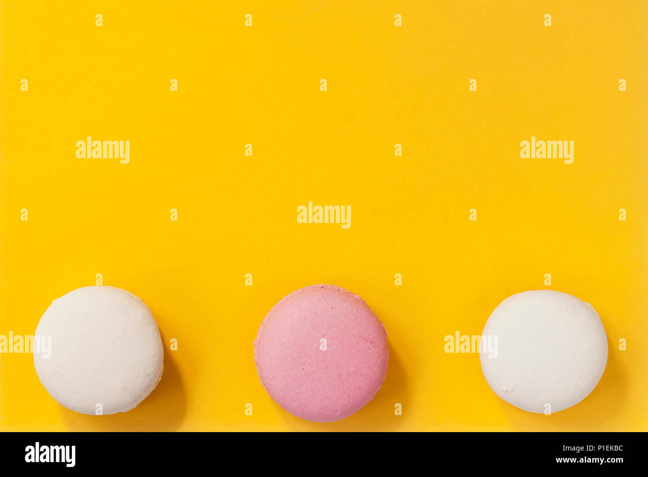 Three macaroons of pink and white colors on yellow background top three macaroons of pink and white colors on yellow background top view romantic morning gift for beloved on easter valentins mothers womens day negle Choice Image
