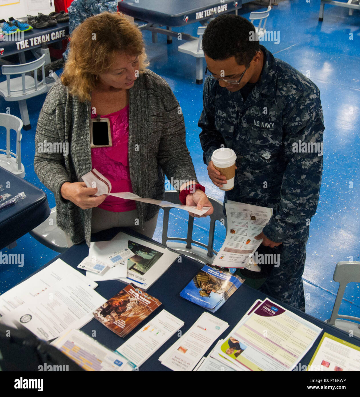 161019-N-OX430-038 NORFOLK (Oct. 19, 2016) Ann Morse, left, a family nurse practitioner at Naval Medical Center Portsmouth (NMCP), provides Seaman James Walsh immunization health care information and research tools during a health promotion and wellness fair held aboard the aircraft carrier USS George H.W. Bush (CVN 77). The health fair provides innovative and evidence-based health promotion and wellness advice to the crew of GHWB. (U.S. Navy photo by Petty Officer 3rd Class Daniel Gaither/Released) - Stock Image