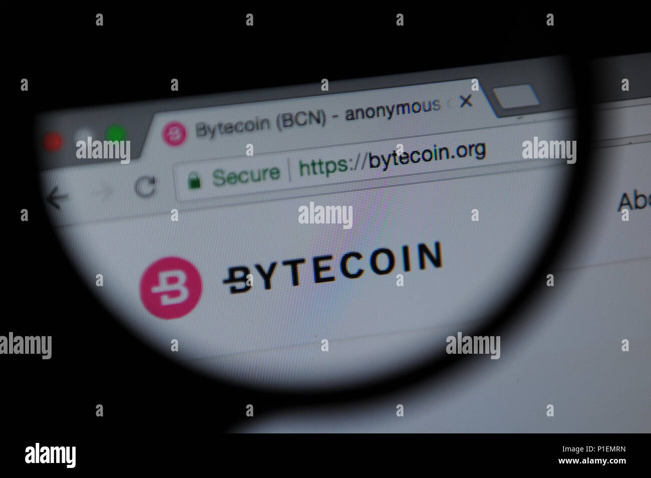 Bytecoin cryptocurrency website seen through a magnifying glass - Stock Image