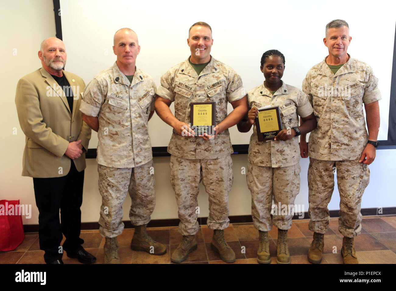 "Essay winners Sgt. Grant Kollinger and Cpl. Jackie Madhava display their plaques while posing with Lt. Gen. Lewis Craparotta, commanding general, I Marine Expeditionary Force (right), Sgt. Maj. Frank Pulley (left), and Sgt. Major Bradley Kasal, during a luncheon for the ""Protect What You've Earned"" essay contest at Marine Corps Base Camp Pendleton, Calif., Oct. 14, 2016. Madhava received first and Kollinger received third place out of more than 40 contestants. (U.S. Marine Corps photo by Pfc. Gabino Perez) - Stock Image"