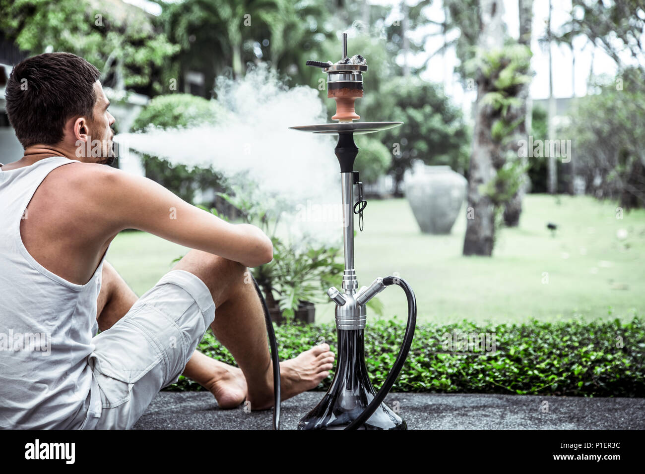 man smoking a hookah on vacation background lifestyle concept - Stock Image