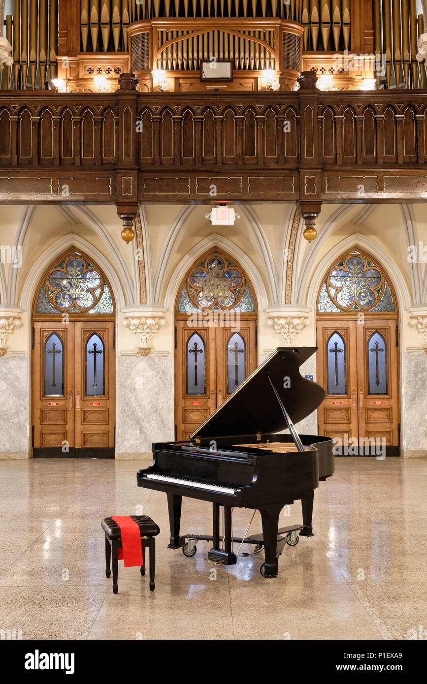Baby grand piano ready to play with open lid in church interior with three beautiful oak doors and stained glass behind, antique circa 1904. - Stock Image