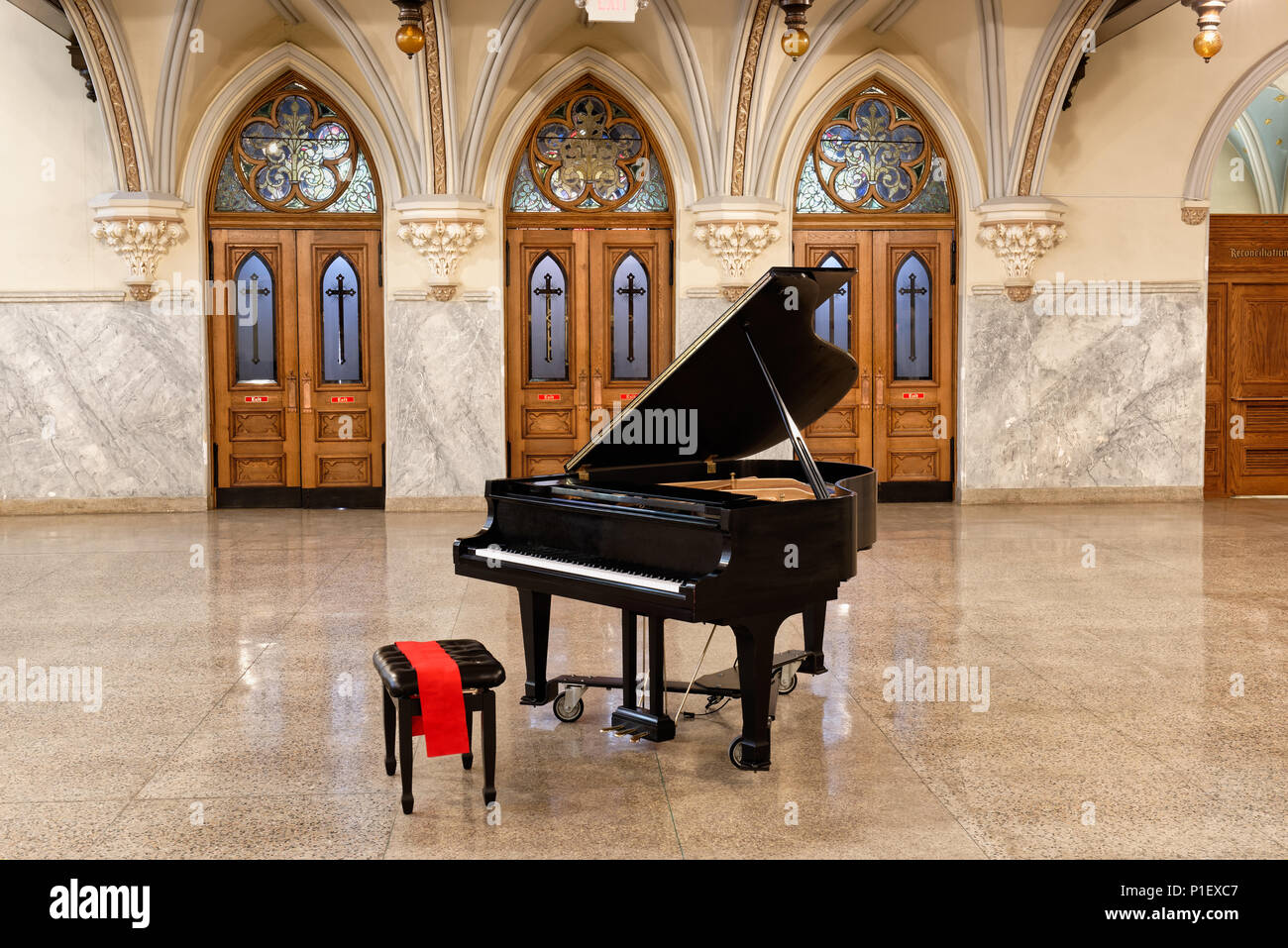 Baby grand piano with open lid in church interior with three beautiful oak doors with stained glass behind, antique circa 1904, Pennsylvania. - Stock Image