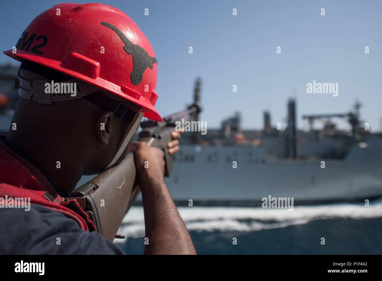 161016-N-DQ503-007    ARABIAN SEA (Oct. 16, 2016) Petty Officer 2nd Class Allen Marshall, prepares to fire a shotline to the fleet replenishment oiler USNS Cesar Chavez (T-AKE 14) from the guided-missile destroyer USS Roosevelt (DDG 80) during a replenishment-at-sea. Roosevelt, deployed as part of the Eisenhower Carrier Strike Group, is supporting maritime security operations and theater security cooperation efforts in the U.S. 5th Fleet area of operations. (U.S. Navy photo by Petty Officer 3rd Class Taylor A. Elberg) - Stock Image