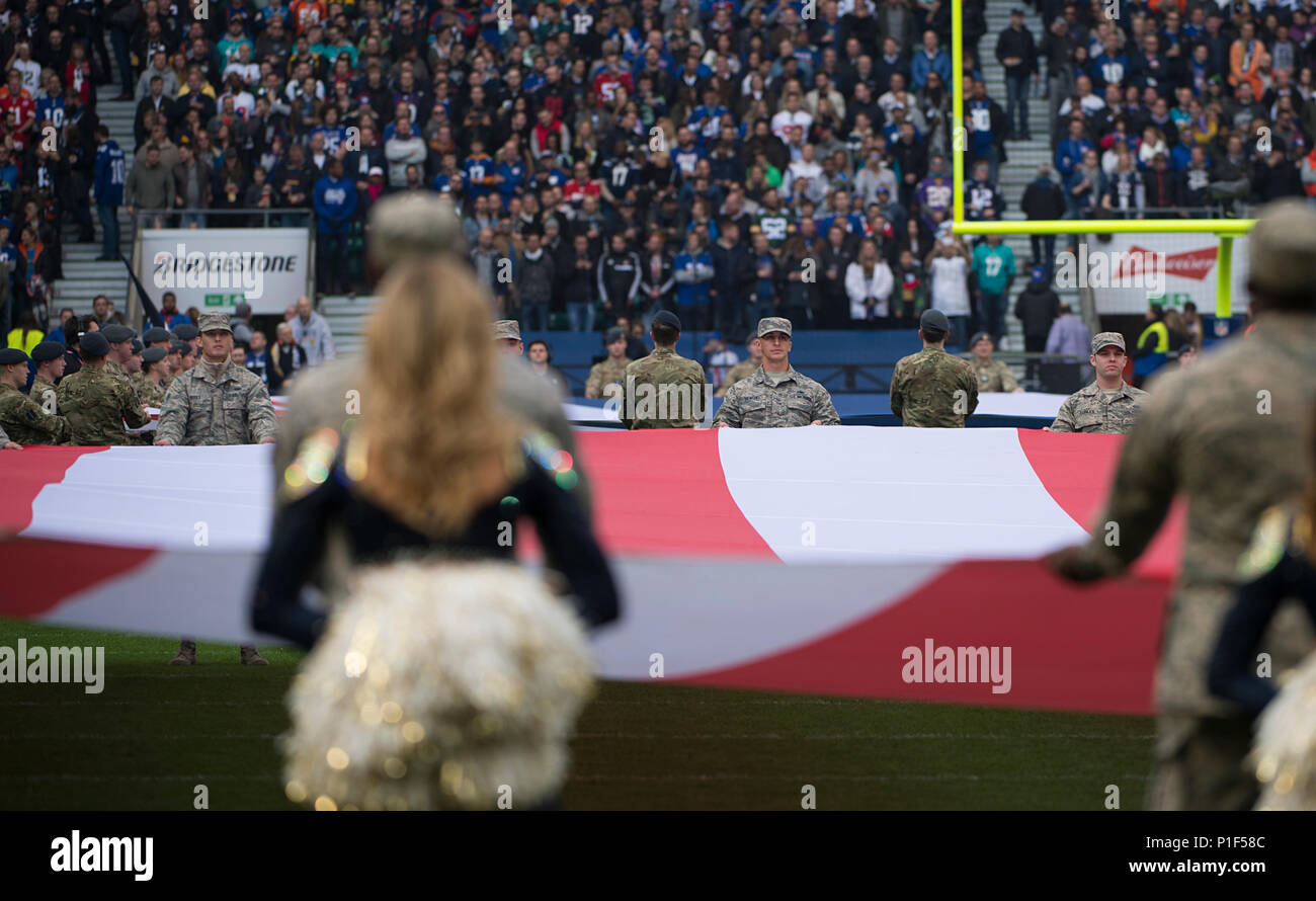 Airmen from Royal Air Force Lakenheath hold the U.S. flag during a pre-game ceremony before the Los Angeles Rams - New York Giants Football game in London, England Oct 23. The game was the second of three international NFL games that will be played this season in London. (U.S. Air Force photo/Staff Sgt. Emerson Nuñez) - Stock Image