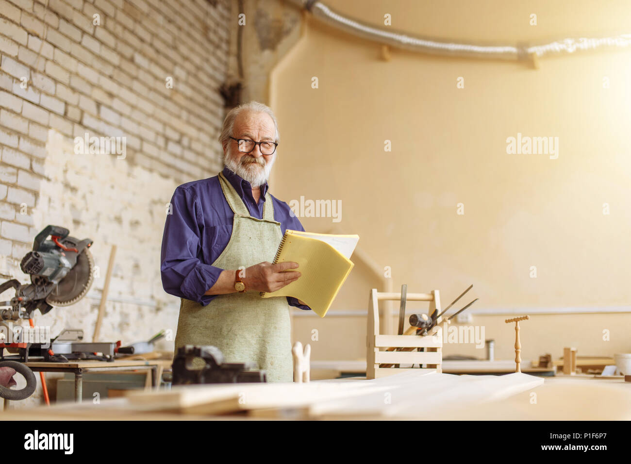 kind grandpa is looking at the camera in the workshop - Stock Image