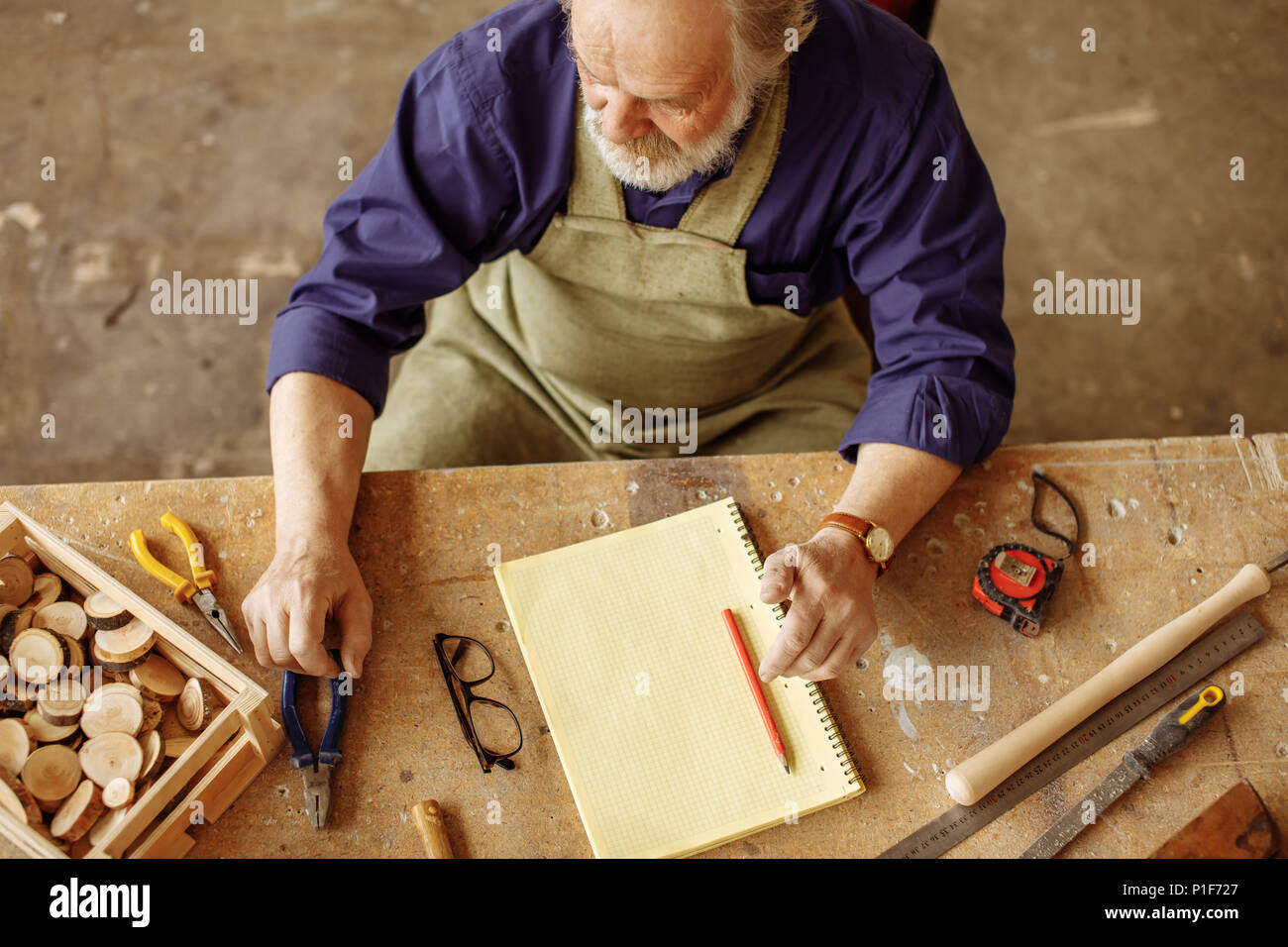 senior citizen sitting at the desk which is cluttered with instruments - Stock Image