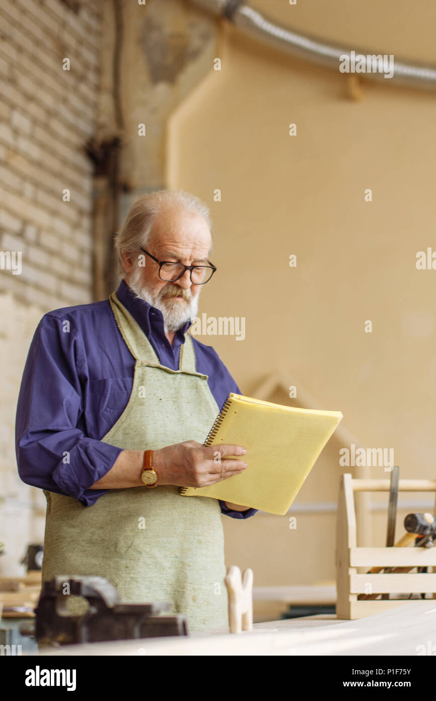 close-up side view shot of elderly man holding exercise book in his workroom - Stock Image