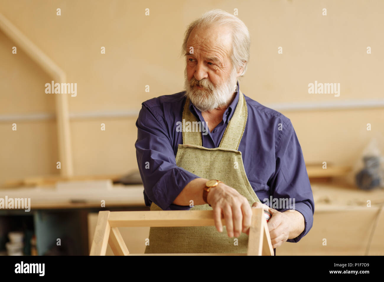 old handsome woodworker standing with serious look in repair shop - Stock Image