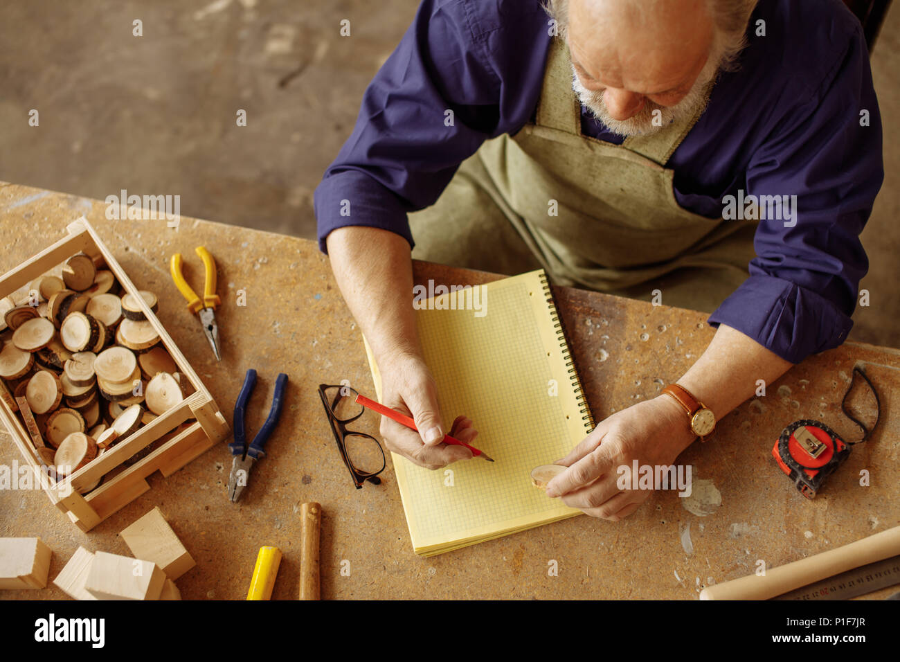 top view shot of old craftsman sitting with pencil and exercise book - Stock Image
