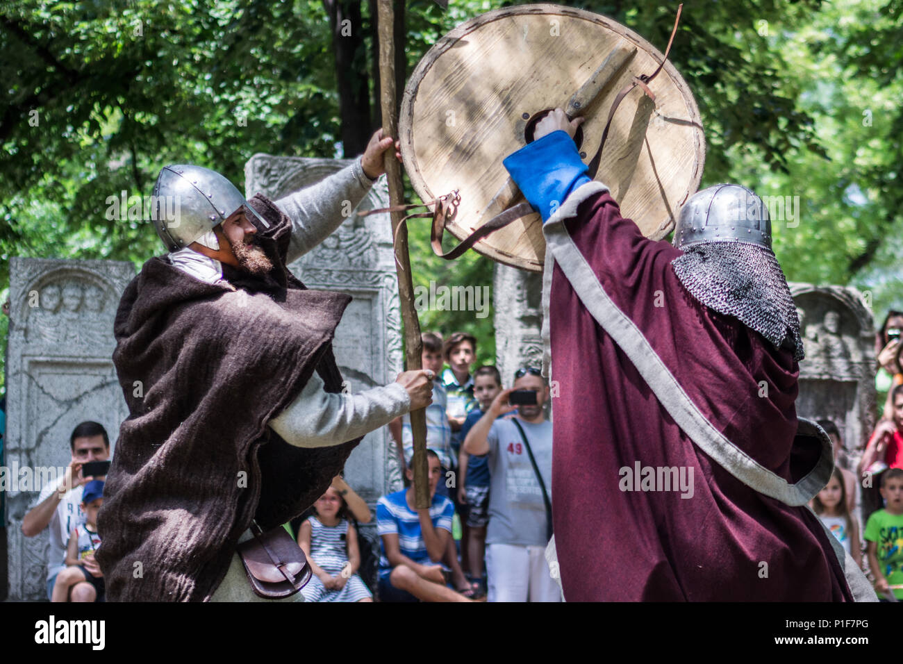 Nis, Serbia - June 10, 2018: Two knights in armor fighting in nature with old weapon. Medieval Festival battle concept Stock Photo