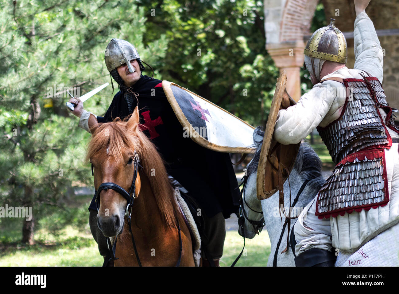 Nis, Serbia - June 10, 2018: Two medieval knight fighting with sword on horses in nature. Middle ages battle concept Stock Photo