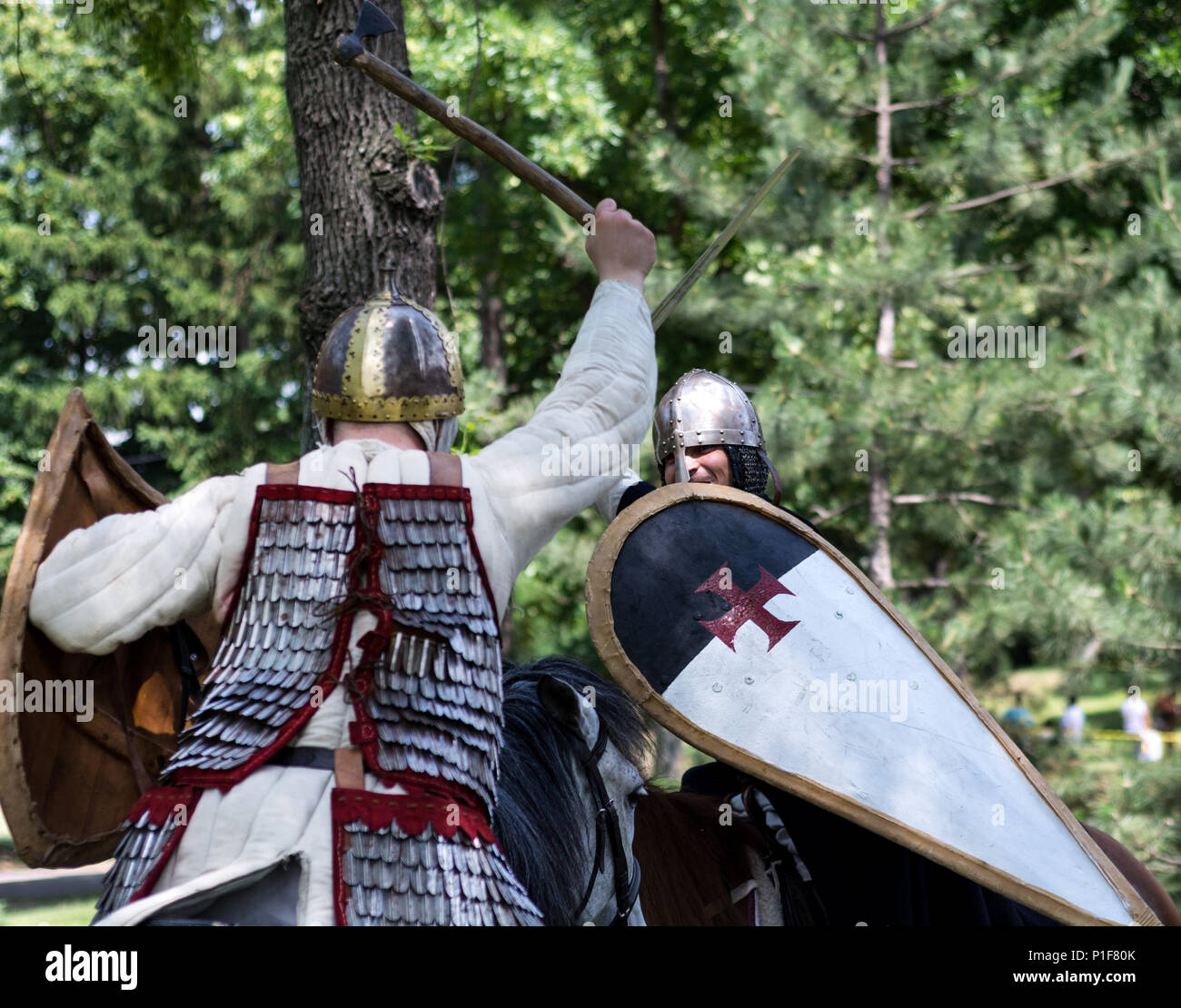 Nis, Serbia - June 10, 2018: Battle of knight on horses with swords in forest. Middle ages fighting concept Stock Photo