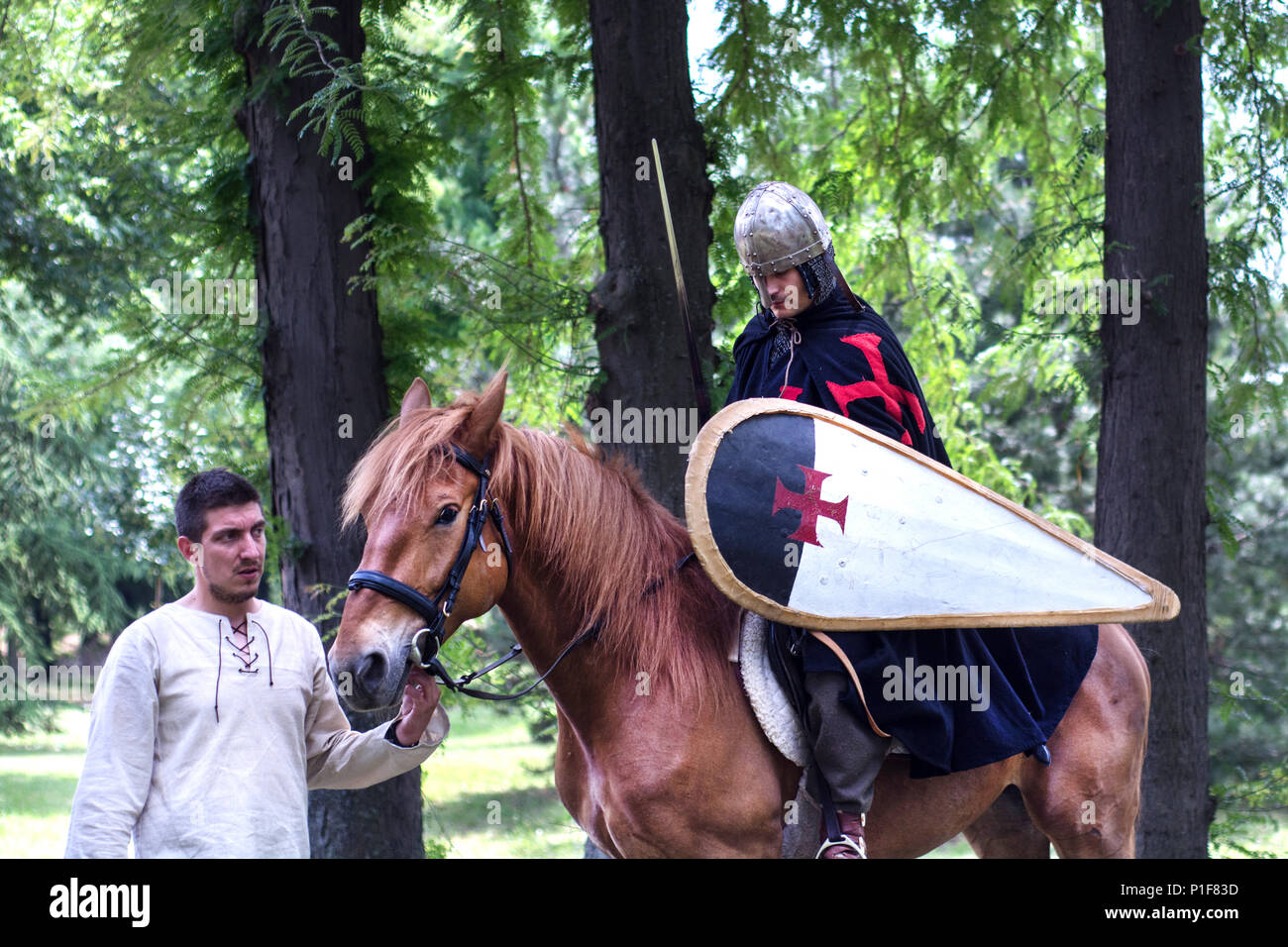 Nis, Serbia - June 10, 2018: Medieval Knight with armor and shield on brown horse and horseman in forest. Middle ages concept Stock Photo